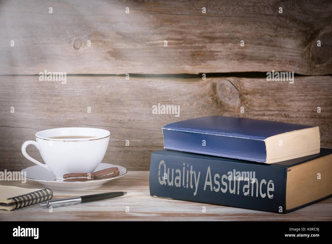 Concept d assurance qualité pile de livres sur le bureau en bois