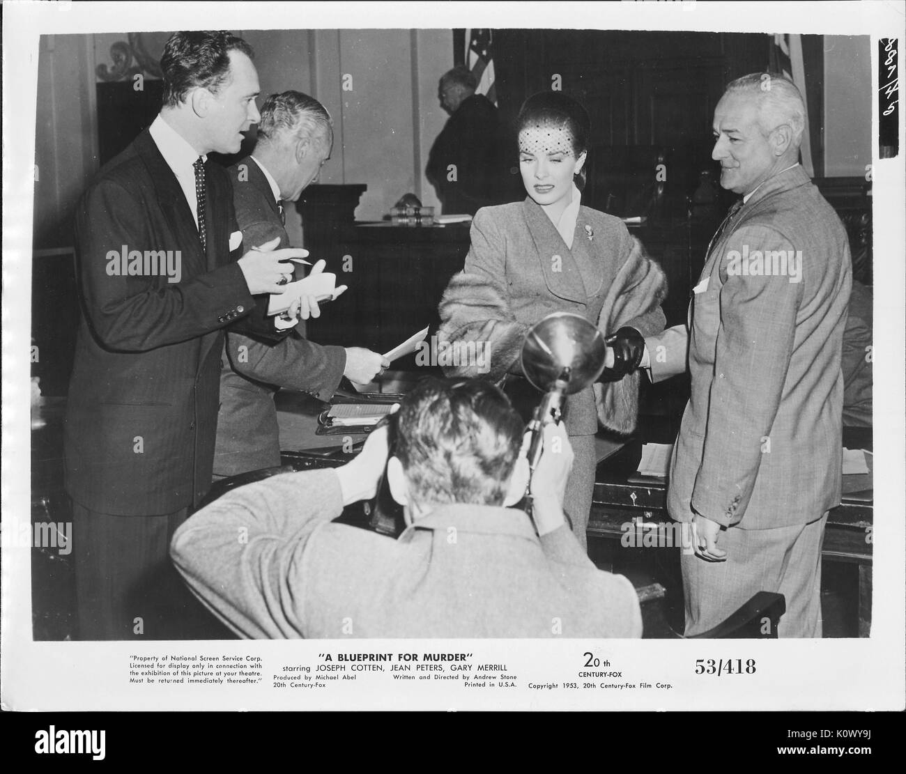 """Encore une scène de film 'un plan de meurtre"""" (1953 20th Century Fox Film thriller), montrant une femme élégante d'être interviewé et photographié par certaines personnes de la presse alors qu'elle s'accrocher à un homme avec des cheveux blancs pour un soutien moral, 1953. Photo Stock"""