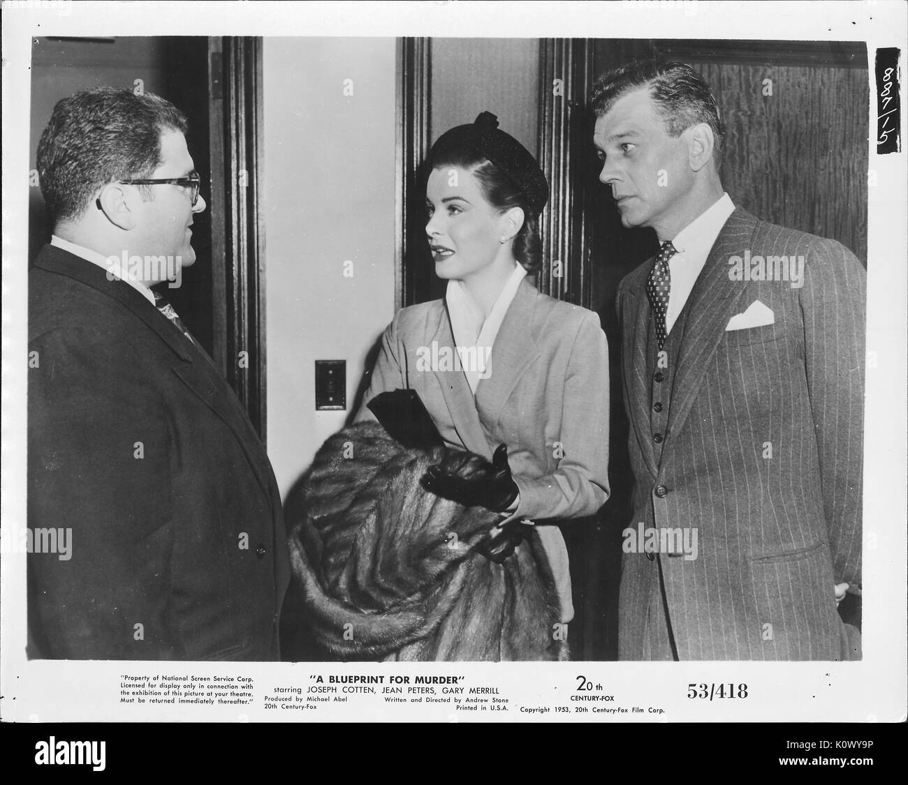 """Encore une scène de film 'un plan de meurtre"""" (1953 20th Century Fox Film thriller), montrant une femme élégante de parler sérieusement d'un homme portant des lunettes et un costume sombre tandis que l'autre homme derrière elle écoute attentivement, 1953. Photo Stock"""