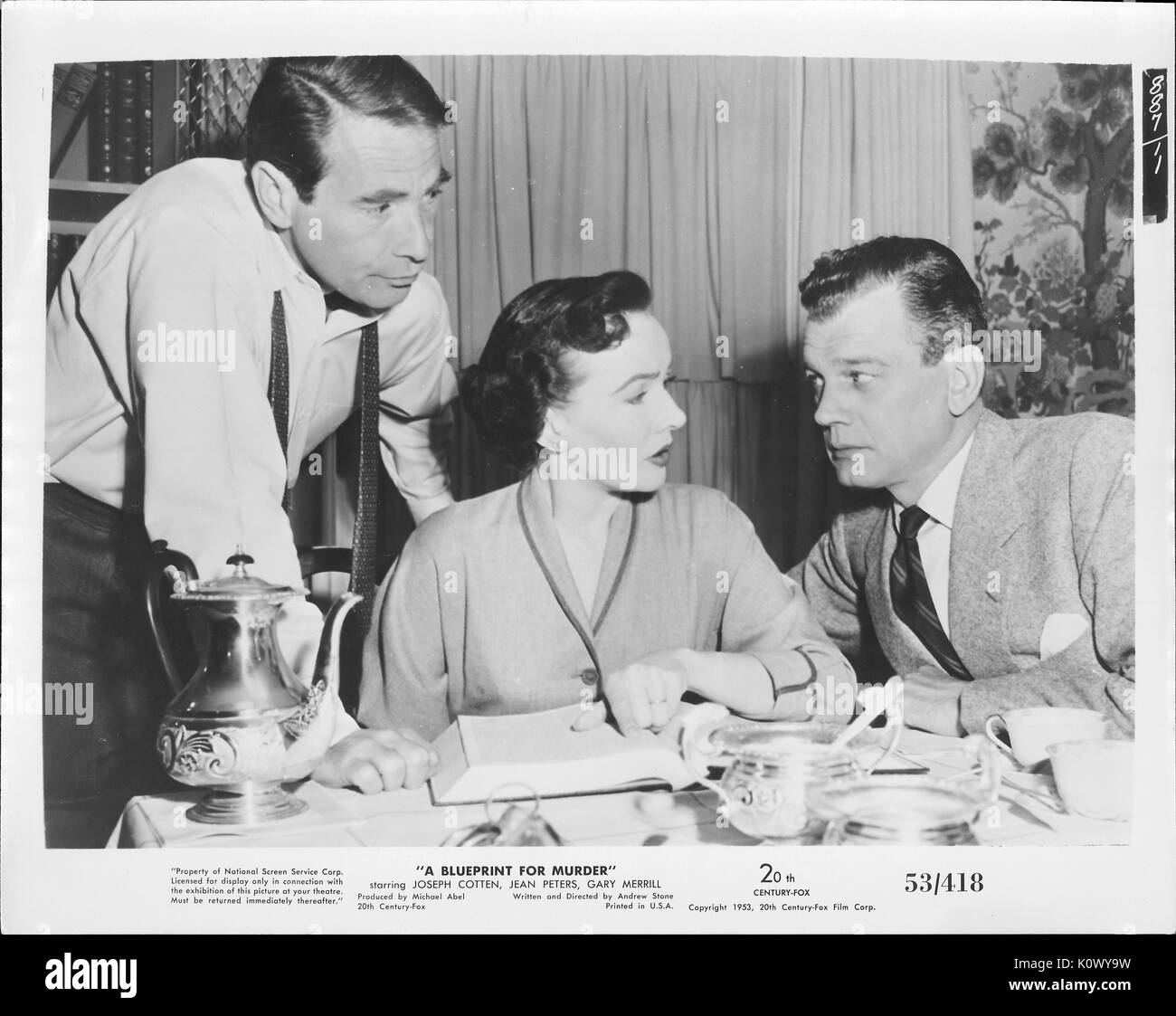 """Encore une scène de film 'un plan de meurtre"""" (1953 20th Century Fox Film thriller), montrant une femme assise faisant remarquer quelque chose dans un livre à l'homme à sa gauche tandis que l'autre homme sur son droit à l'écoute, 1953. Photo Stock"""