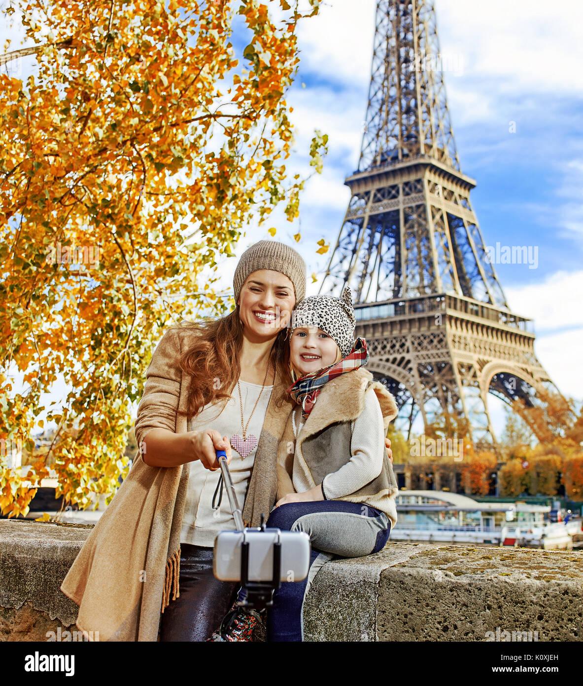 Escapades d'Automne à Paris avec la famille. smiling mother and child les voyageurs sur le quai à Paris, France en prenant l'aide de bâton selfies selfies Photo Stock