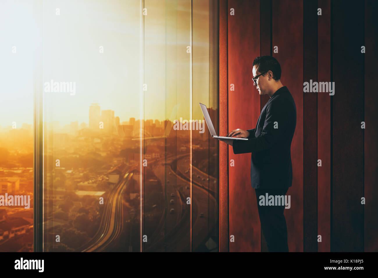 Businessman using laptop avec arrière-plan de bureau génériques , scène de nuit . Photo Stock