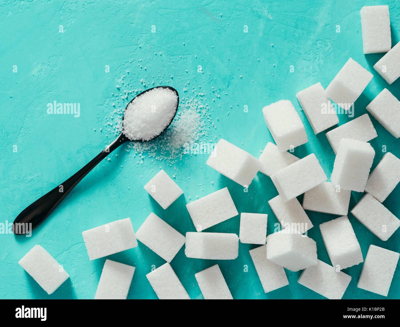 Contexte de cubes de sucre et de sucre dans une cuillère. Sucre blanc sur fond bleu turquoise. Le sucre à l'exemplaire de l'espace. Vue supérieure ou télévision lay Photo Stock