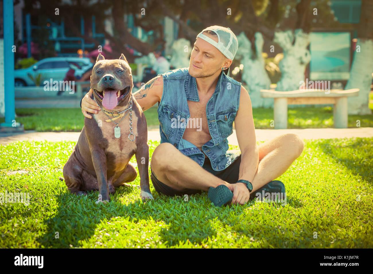 L'homme et le chien bull-terrier américain de mine de détente à l'initiative Faire place au parc et s'étreindre Photo Stock