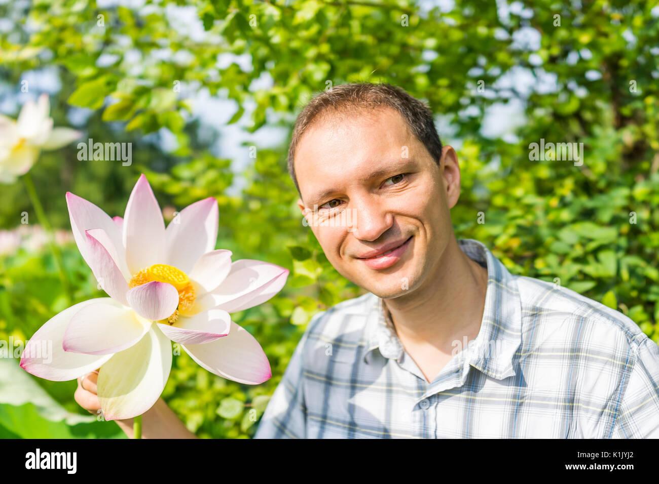 Gros plan Portrait of young man smiling holding Bright White Rose et fleur de lotus avec l'intérieur de la graine jaune Photo Stock