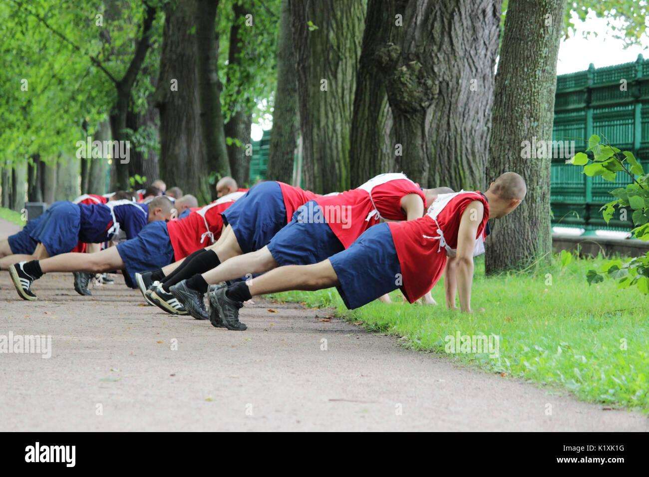 Groupe d'athlètes masculins de faire du sport dans la rue, pour éliminer du sol. Photo Stock