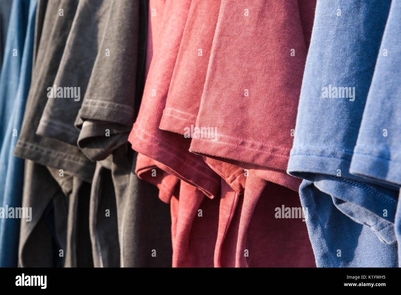 Bleu, rouge et gris foncé t-shirts hang d'affilée sur l'affichage pour la vente à une piscine extérieure locale équitable. Vue rapprochée. Photo Stock