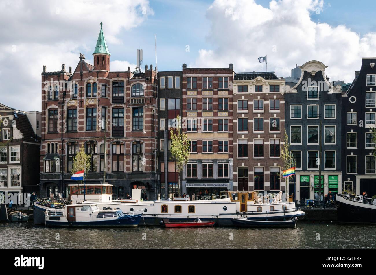 Amsterdam, Pays-Bas - 27 avril, 2017: péniches et barges vivant dans Binnenamstel contre canal néerlandais typiques maisons avec pavillon de l'Allemagne et Banque D'Images