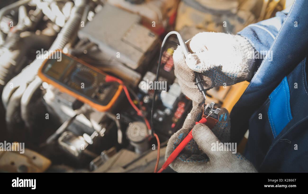 Mécanicien dans l'atelier automatique fonctionne avec location de l'électrique - câblage électrique, voltmètre - Vue de dessus Photo Stock