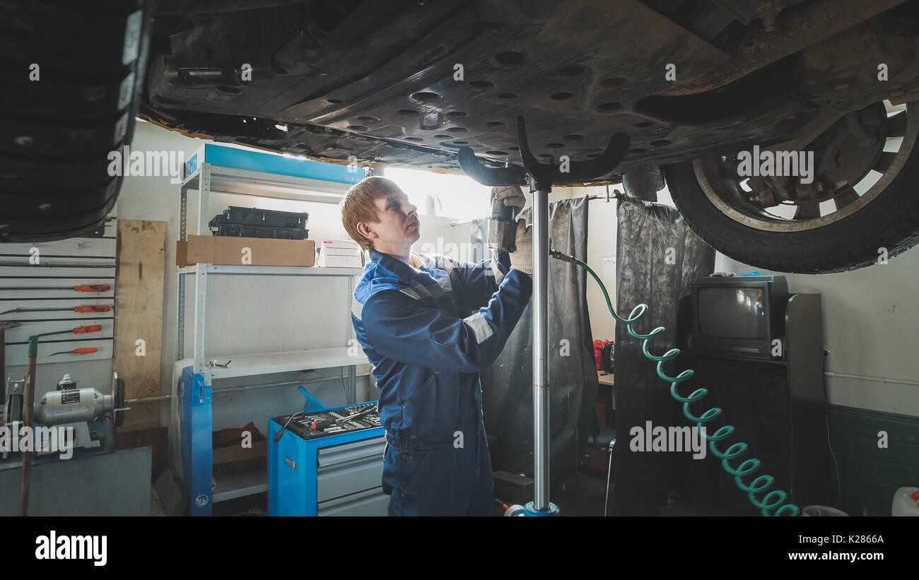 Mécanicien travailleur dévissant de pièces d'automobile voiture levée sous fond Photo Stock