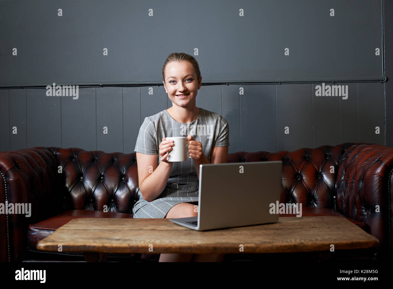Portrait Of Businesswoman Working On Laptop In Internet Cafe Photo Stock