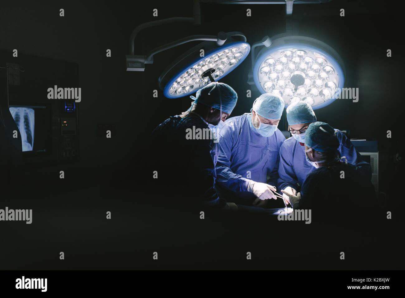 L'équipe médicale d'effectuer la chirurgie. Groupe des chirurgiens en salle d'opération de l'hôpital. Photo Stock