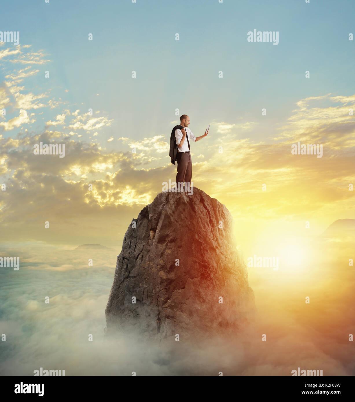 Businessman fonctionne sur tablette avec connexion internet sur une montagne Photo Stock
