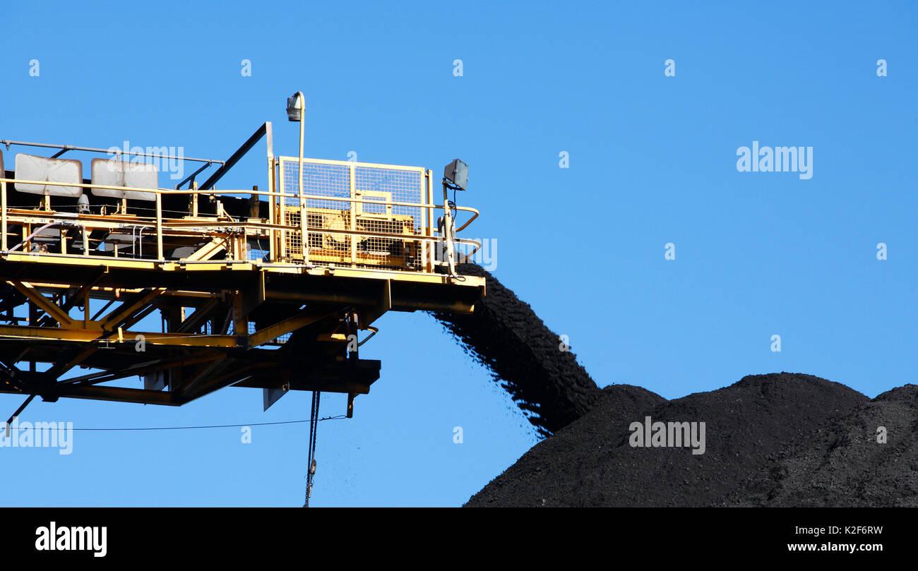 Courroie du convoyeur de charbon jaune transportant du charbon et verser sur un pieu, Australie Photo Stock