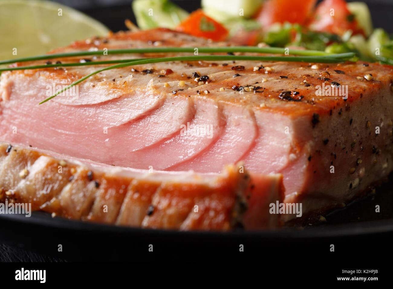 Steak de thon grillé au poivre macro sur une plaque horizontale. Photo Stock