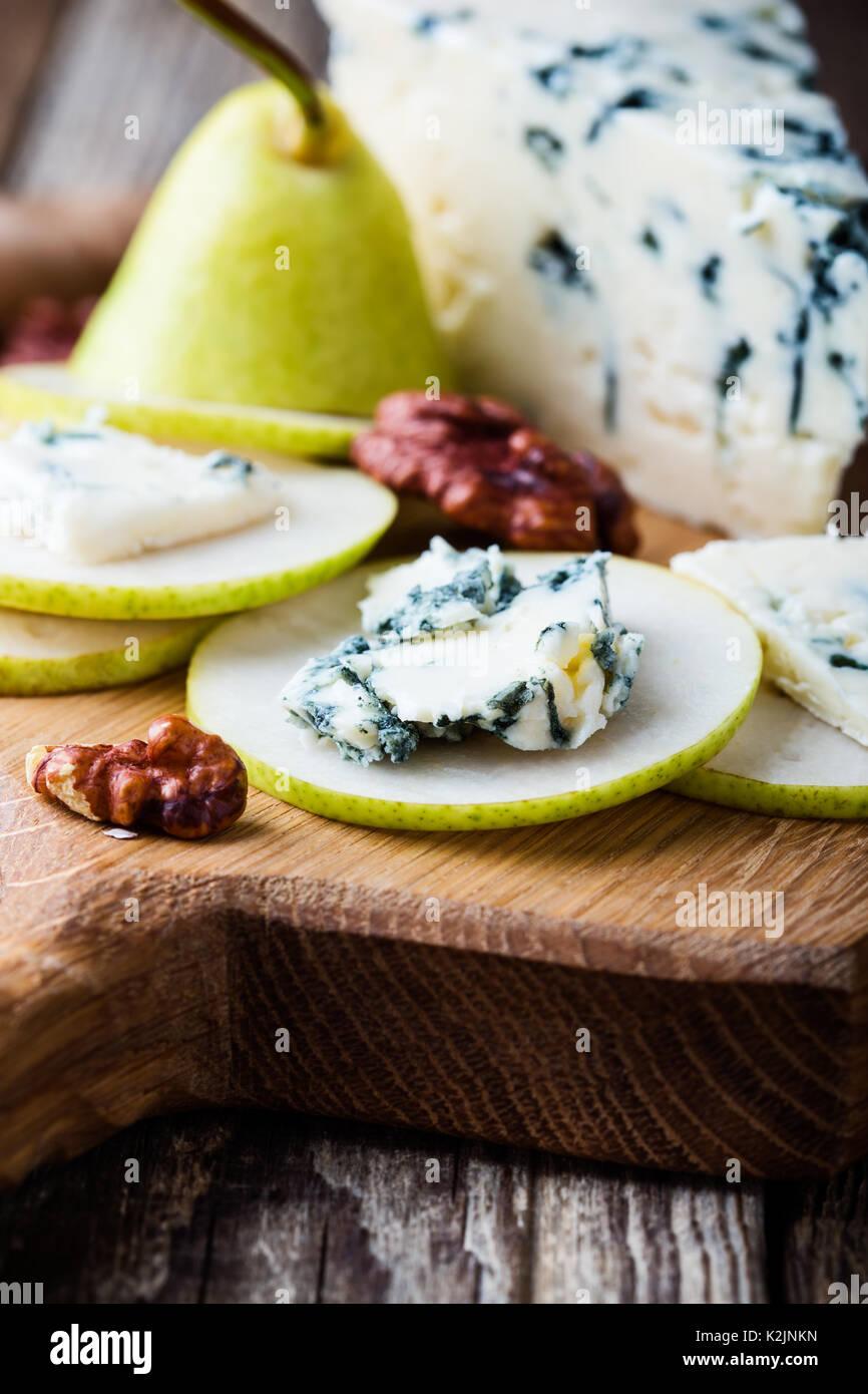 Plateau de fromages. Fromage bleu avec poire fraîche sur planche de bois rustique Photo Stock