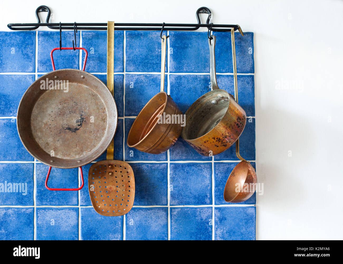 Cuisine intérieur avec vintage ustensile en cuivre. L'ensemble de cuisson à l'ancienne. Pan, cuillère, skimmer hanging on blue tile wall. Copie espace, fond blanc Photo Stock