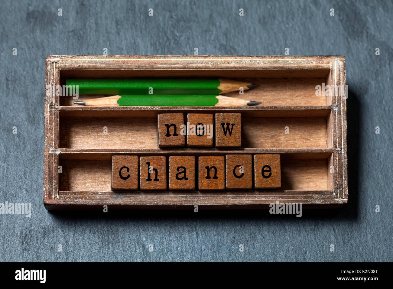 Nouvelle chance de phrase. La motivation et les attentes positives concept. Boîte en bois vintage, des cubes avec des lettres de style ancien, crayons vert. Fond texturé en pierre grise. Close-up, up vue, soft focus Photo Stock