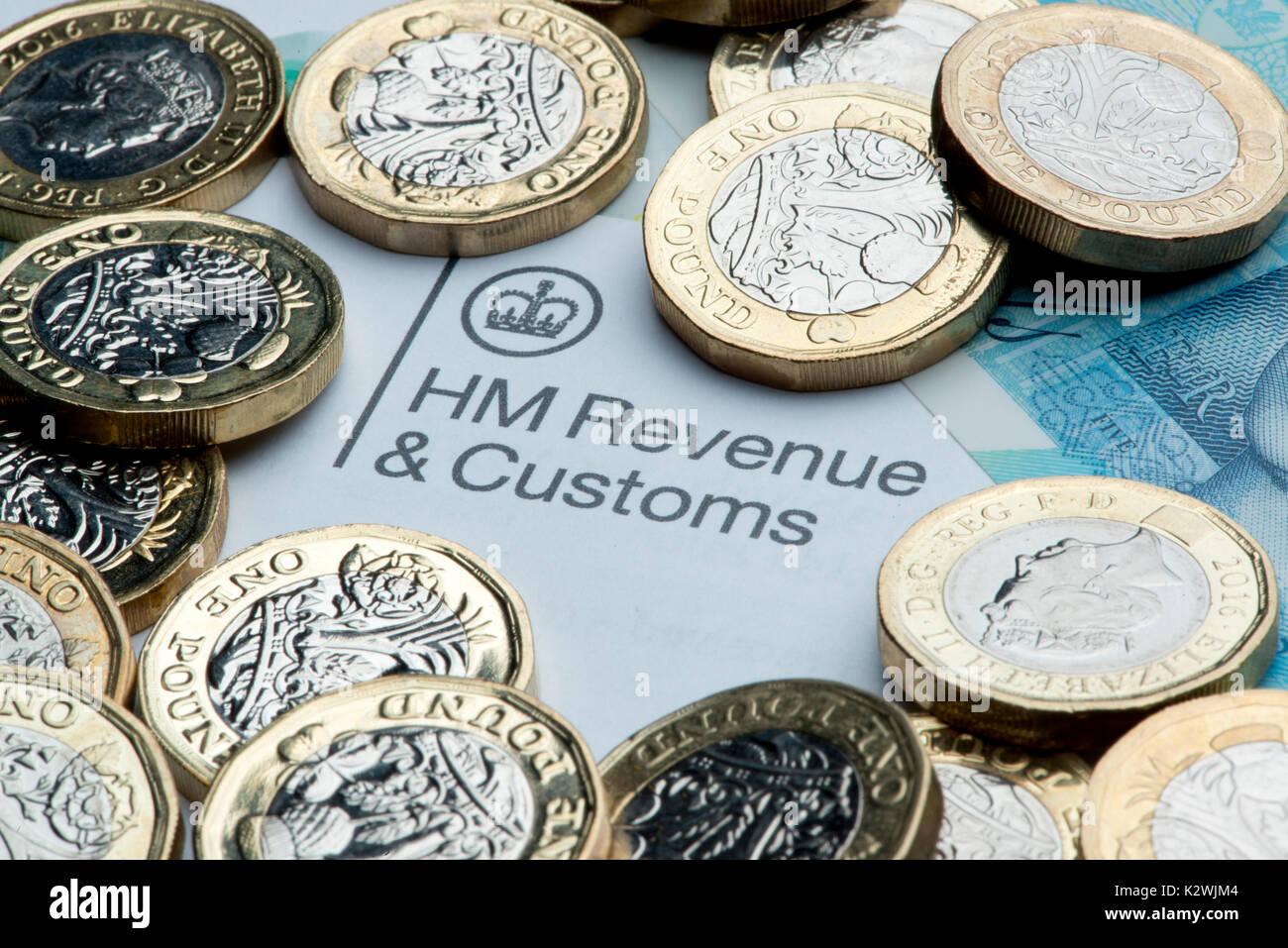 Un chiffre d'HM et Douanes en-tête entourée par de nouveaux €1 €5 pièces de monnaie et une note. Photo Stock