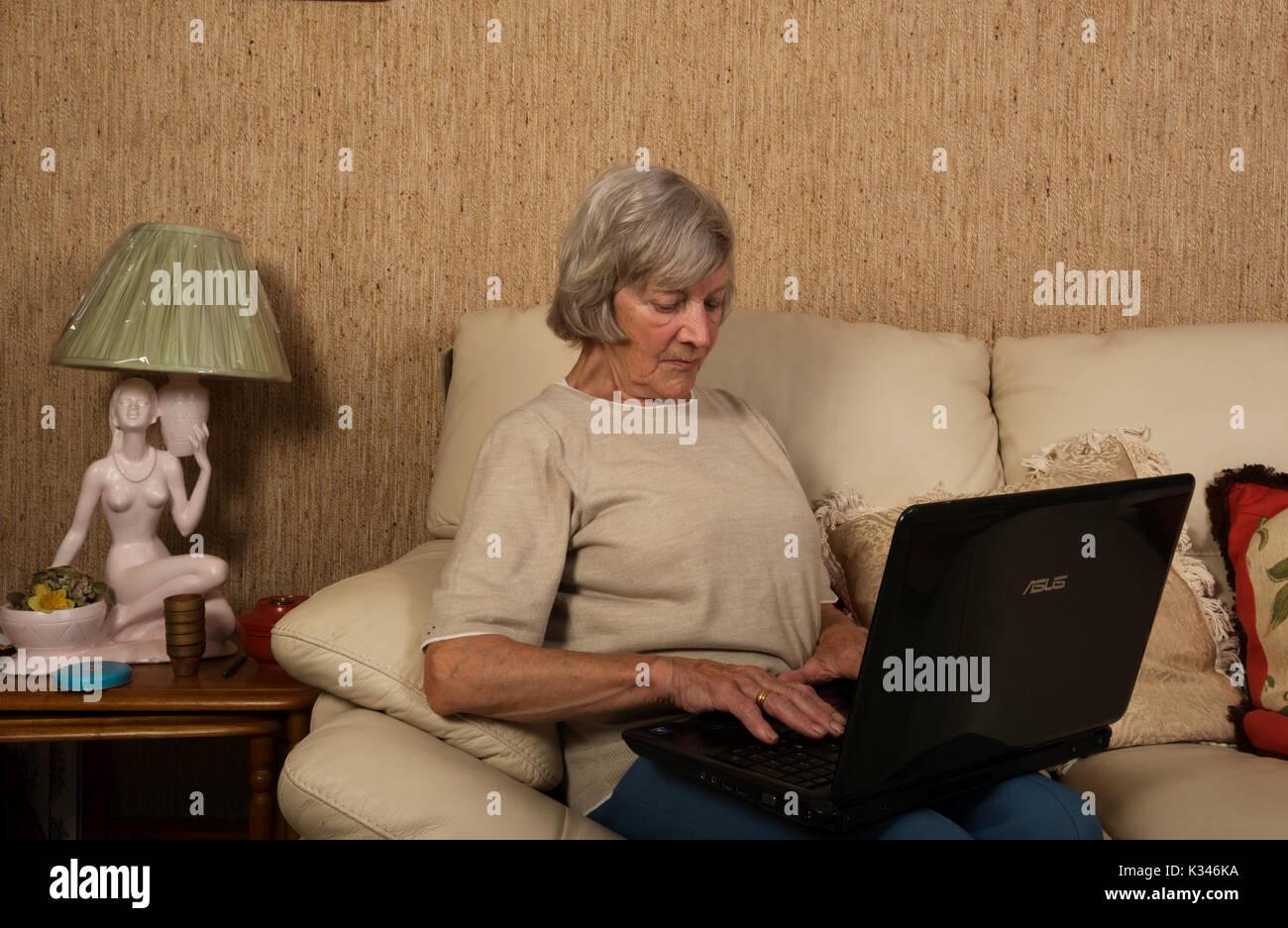 8eeba8297bf3b Femme âgée à l'aide d'un ordinateur portable pour faire des achats en