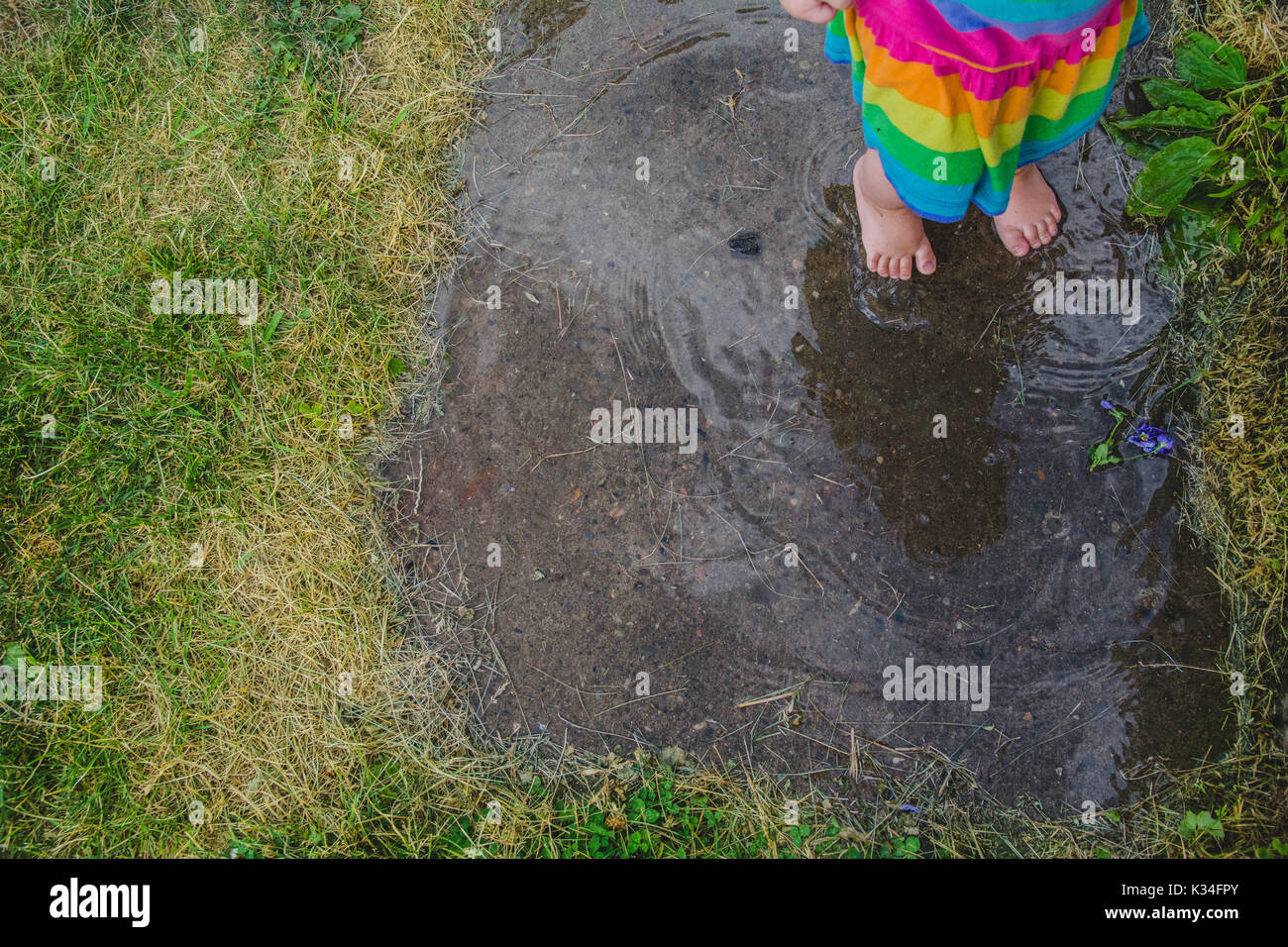 Un jeune enfant se trouve dans une flaque de boue un jour de pluie. Photo Stock
