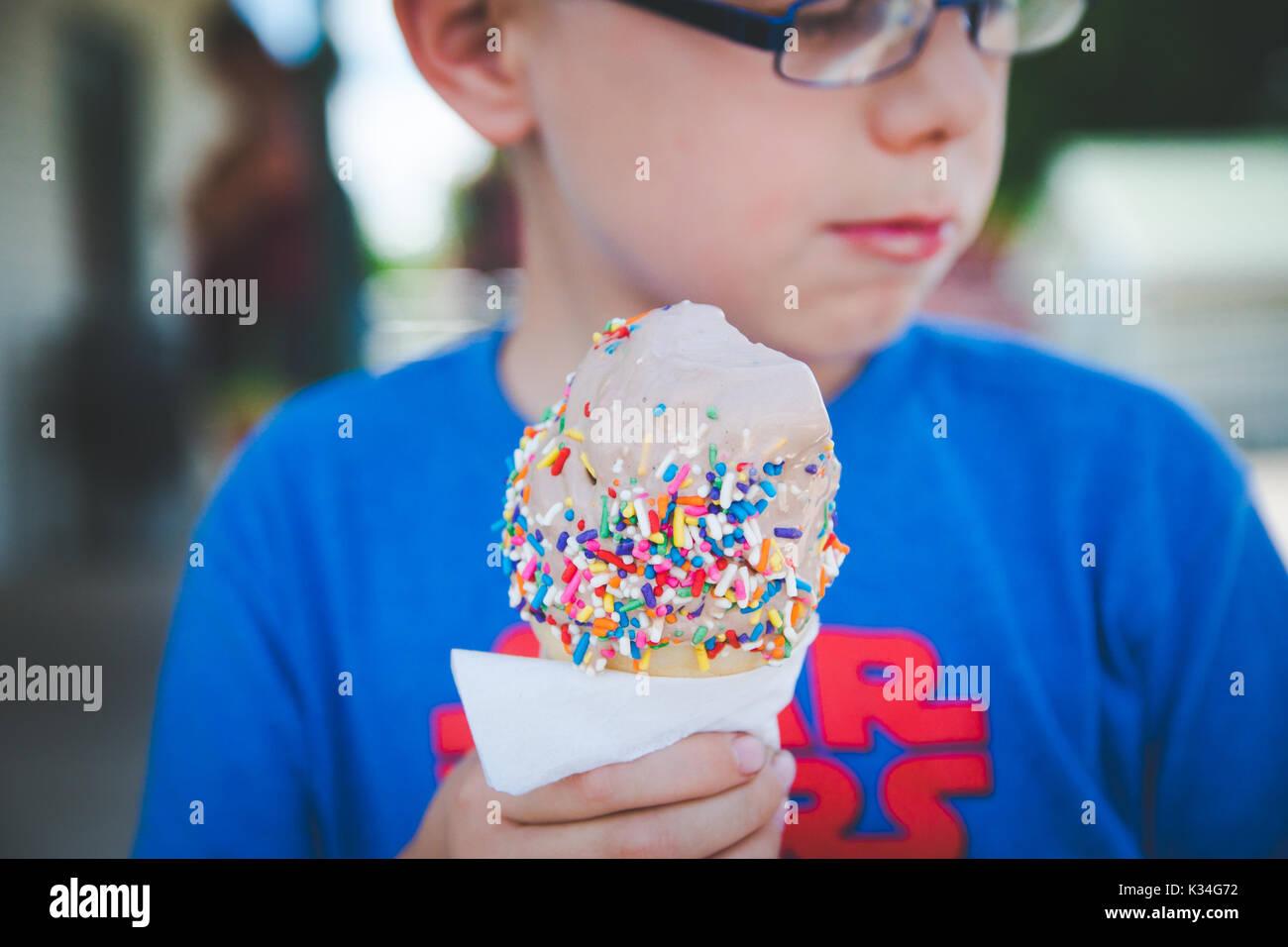 Un garçon mange un cornet de crème glacée pendant une saison chaude. Photo Stock