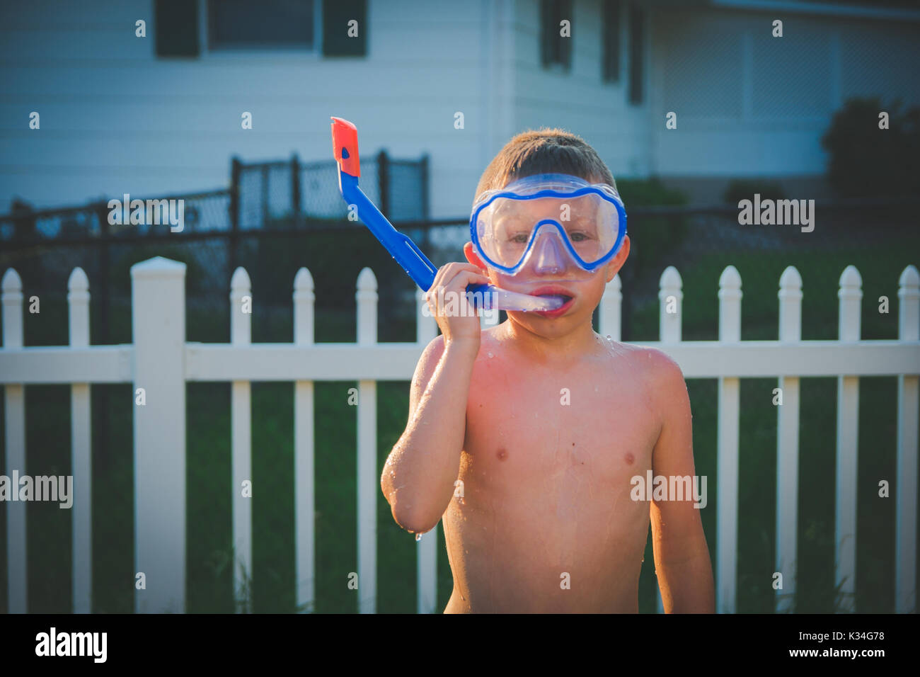 Un garçon porte un masque de plongée dans une arrière-cour pendant l'été. Photo Stock