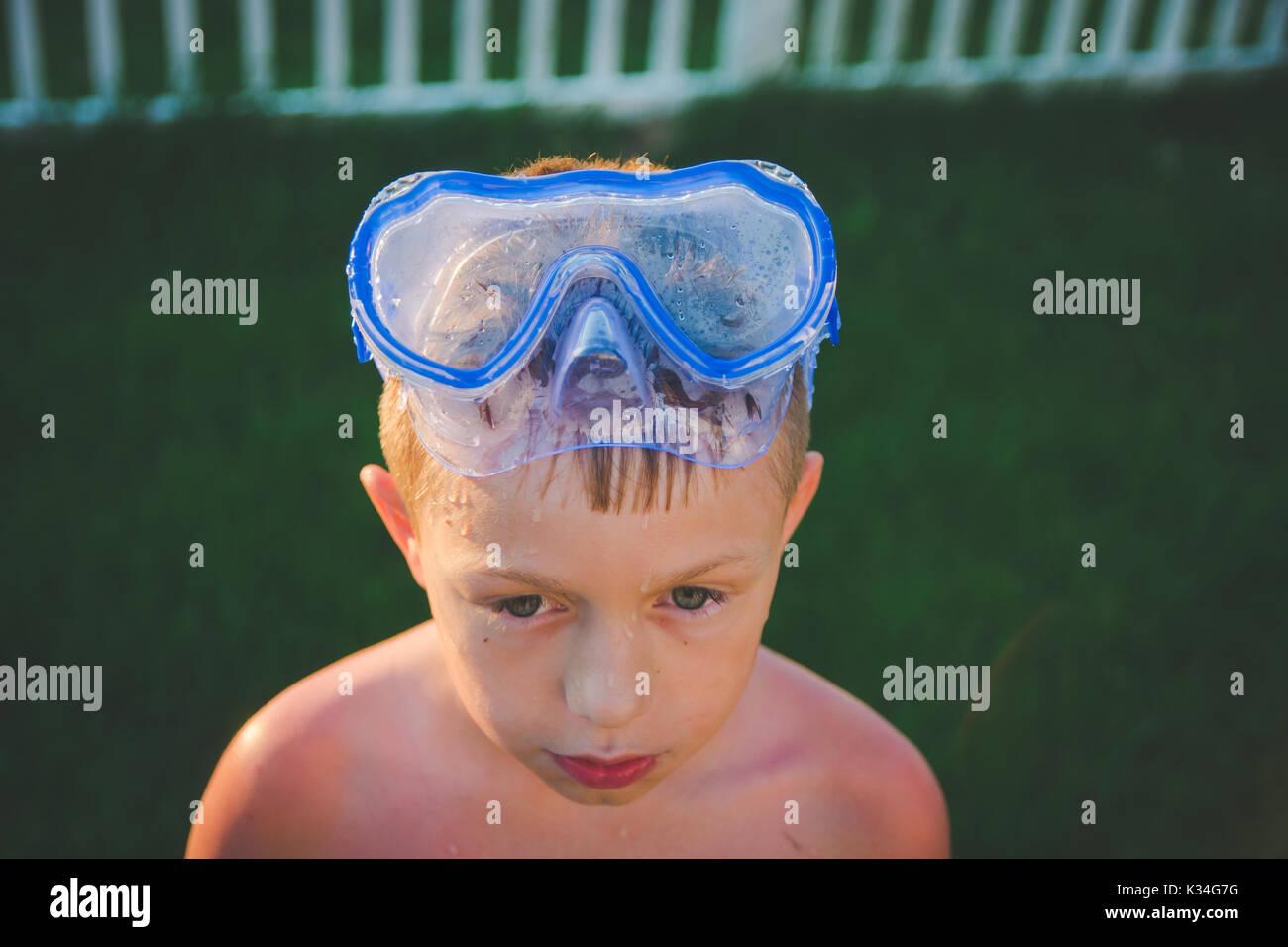Un garçon porte un masque de plongée sur la tête pendant l'été alors que le soleil brille sur lui. Photo Stock
