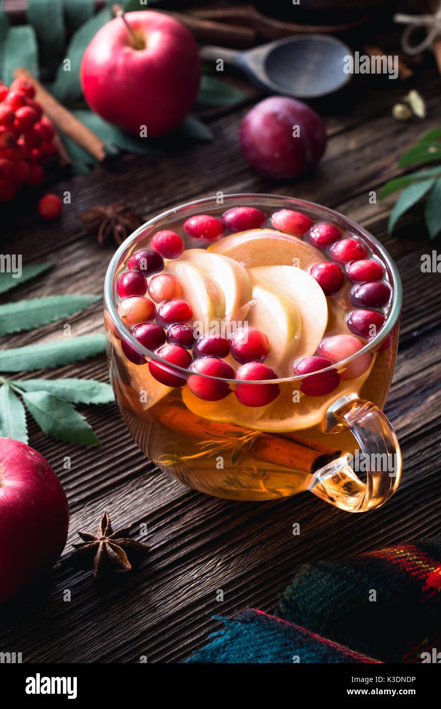 Plateau de fruits d'hiver au réchauffement et aux canneberges, pommes, cannelle, citron, miel et thym dans une tasse en verre sur la table en bois composition verticale. Photo Stock