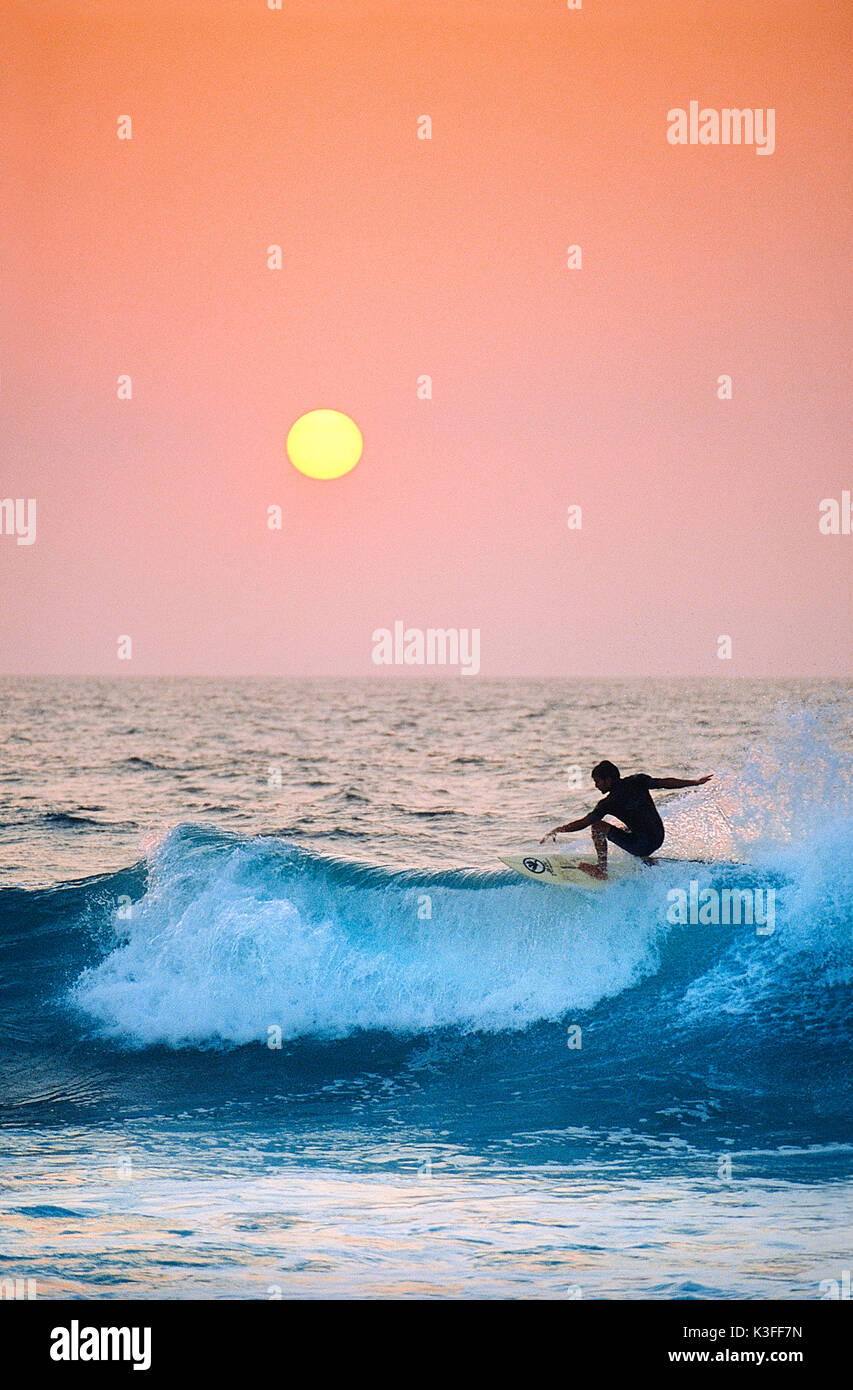 Surfer en face du soleil couchant soleil Photo Stock