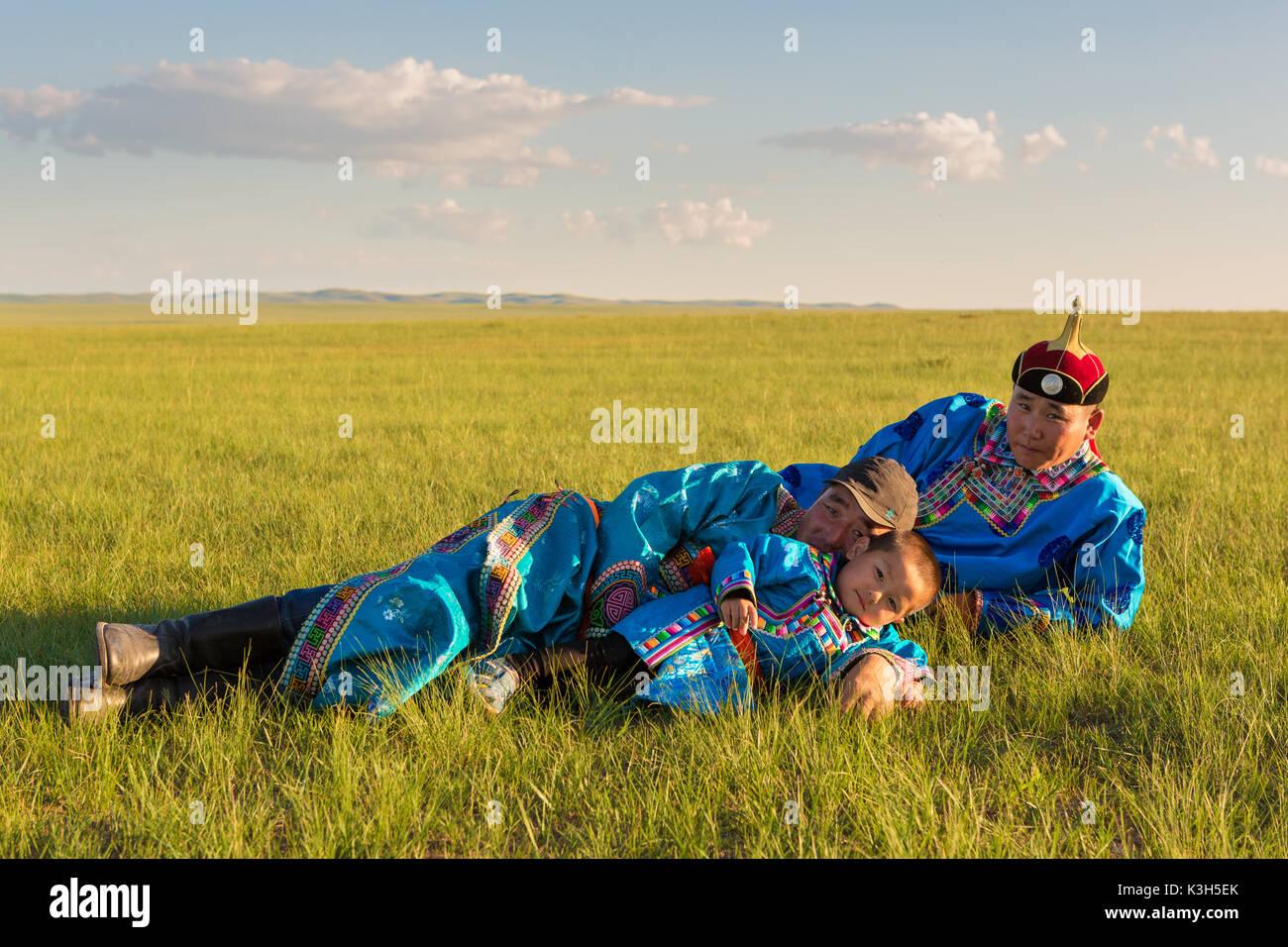En Mongolie intérieure, Chine-juillet 30, 2017: la famille mongole nomade avec leurs robes colorées près de leur maison à la prairie immense du pays Photo Stock
