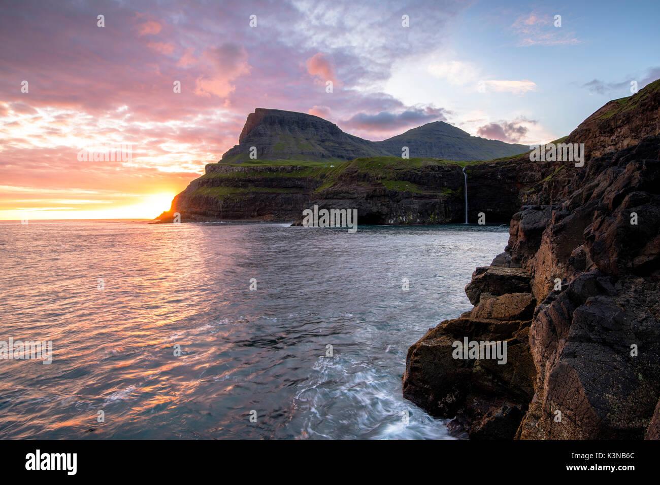 Gasadalur, Vagar et Île, Îles Féroé, Danemark. La célèbre cascade d'un saut d'la falaise dans l'océan au coucher du soleil. Photo Stock