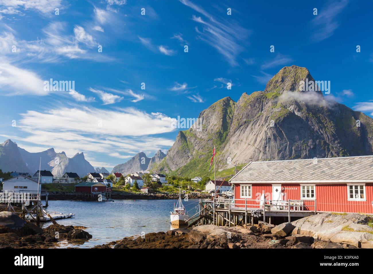 Maison typique de pêcheurs appelée Rorbu encadrée par des pics rocheux et d'une mer bleue Reine Lofoten, Norvège Europe Moskenes Photo Stock