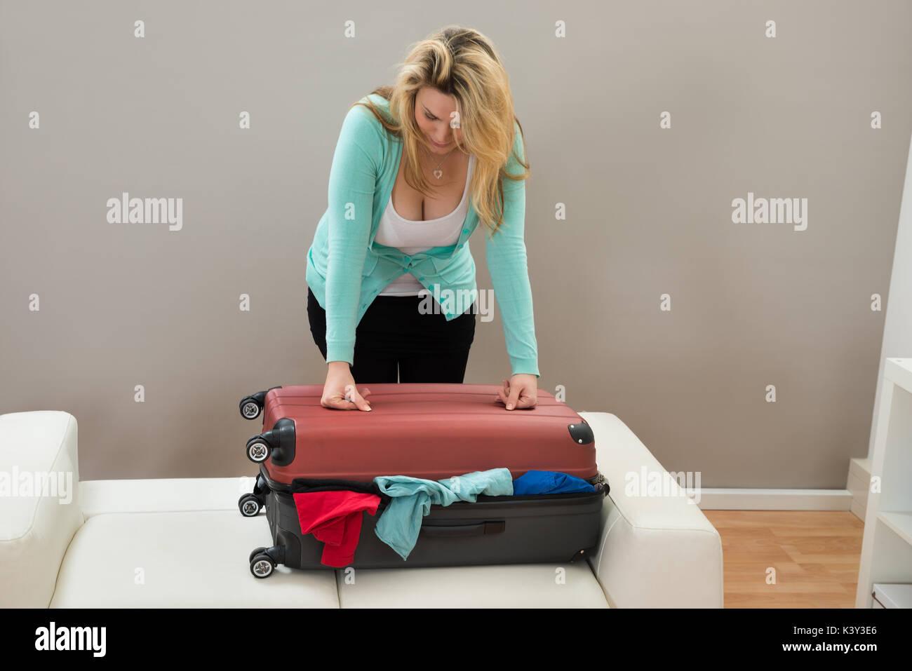 Femme essayant de fermer la valise remplie dans la chambre Photo Stock