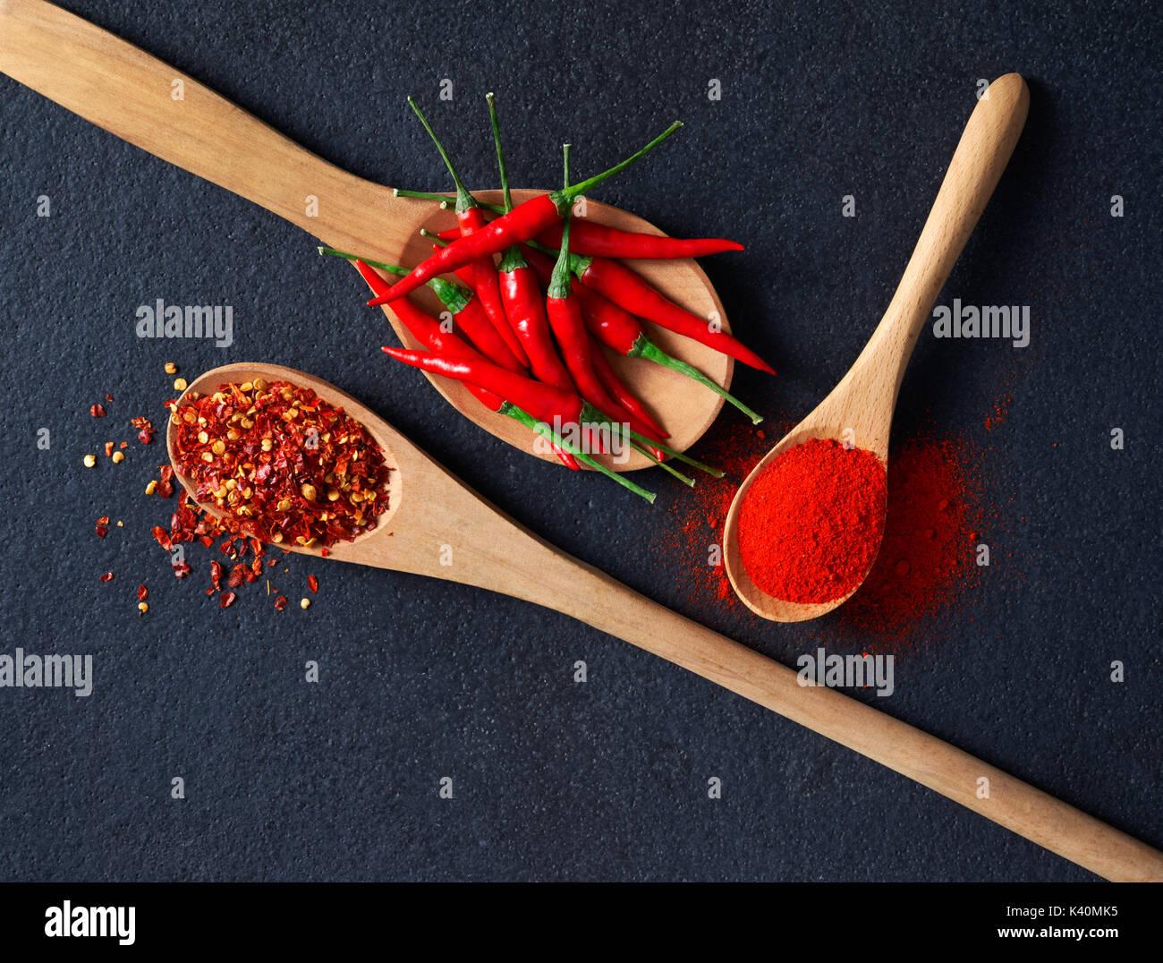 Cuillère en bois remplis de piment, de flocons de poivron rouge et de piment en poudre Photo Stock
