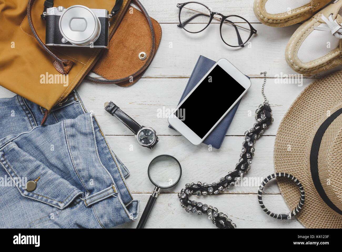Vue de dessus accessoires de voyager avec des vêtements femmes concept. wallet sur fond de bois.watch,chapeau,ordinateur portable camera,collier et ses chaussures sur bois blanc Photo Stock