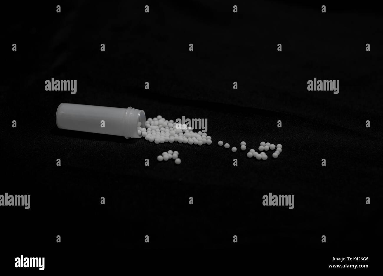 Une bouteille de médicament homéopathique comprimés étant renversé sur une table Photo Stock