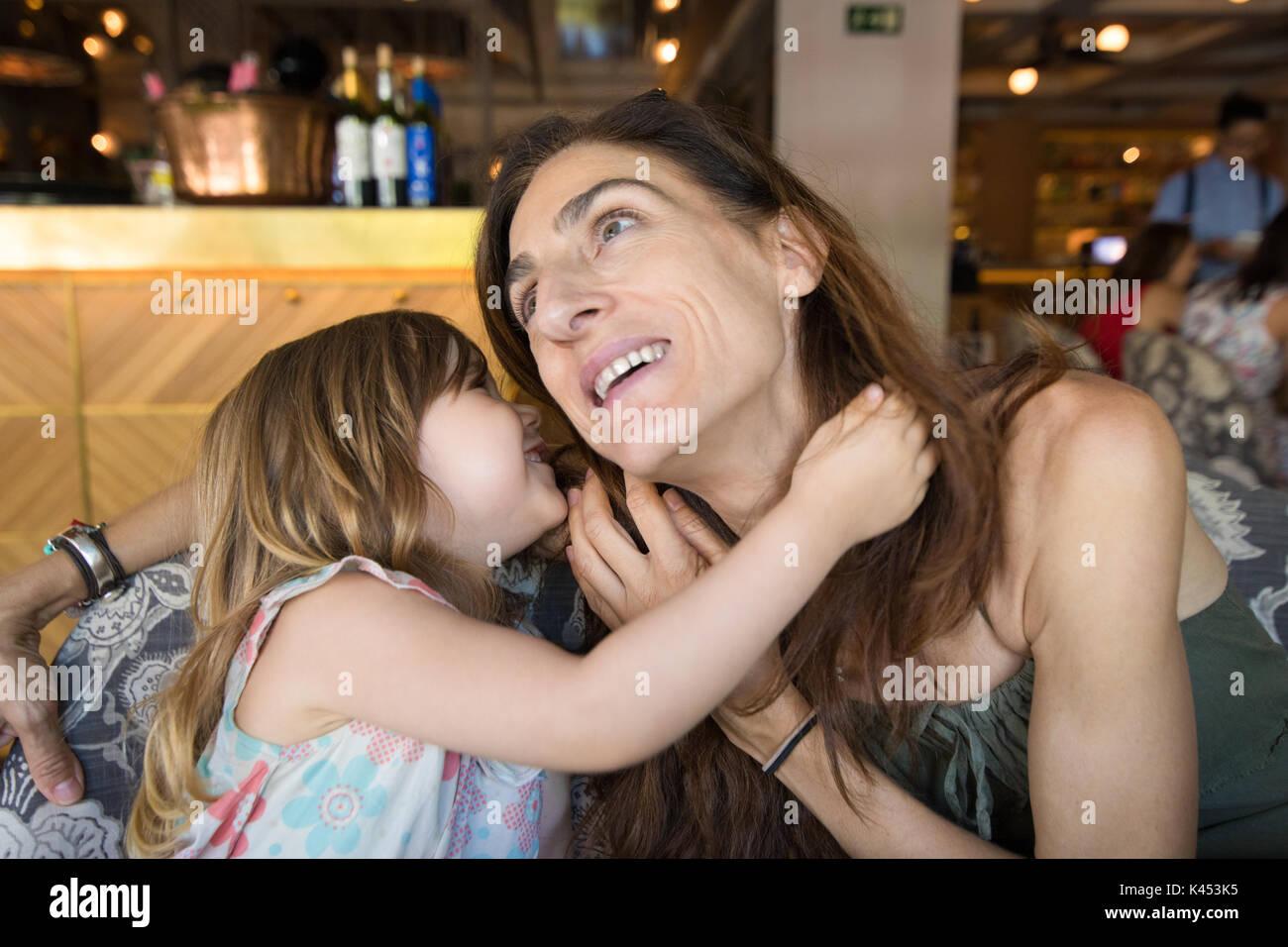 Trois ans fille blonde parler dans l'oreille de femme mère sitting in restaurant Photo Stock