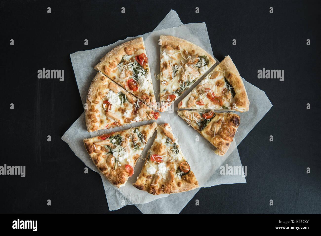 Vue de dessus de la cuisine italienne traditionnelle pizza tranché sur parchemin sur surface sombre Photo Stock