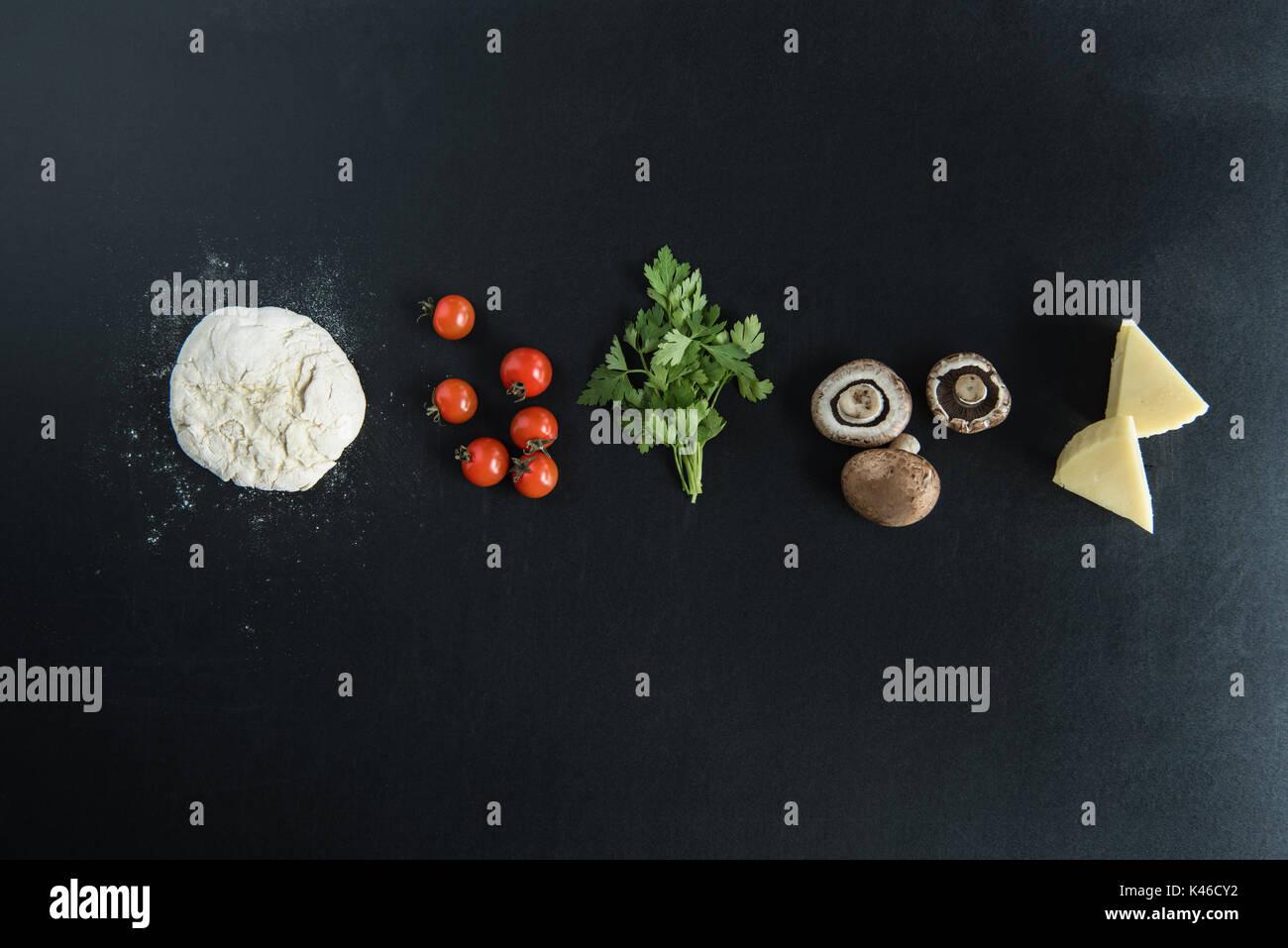 Vue de dessus de la pâte avec les ingrédients pour la préparation de pizza italienne sur la surface sombre Photo Stock