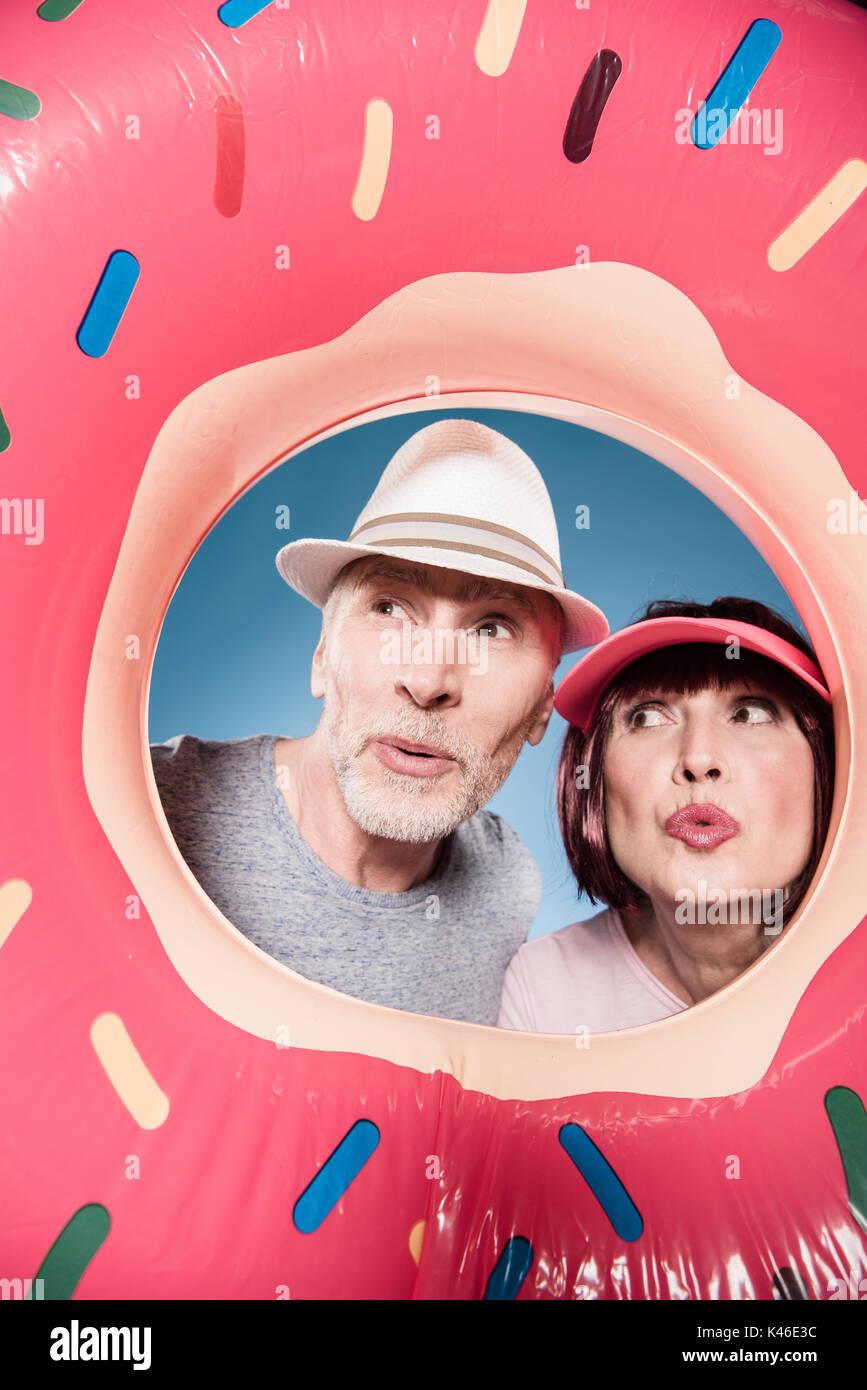 Couple de personnes âgées élégant avec l'expression du visage en tube de natation Photo Stock