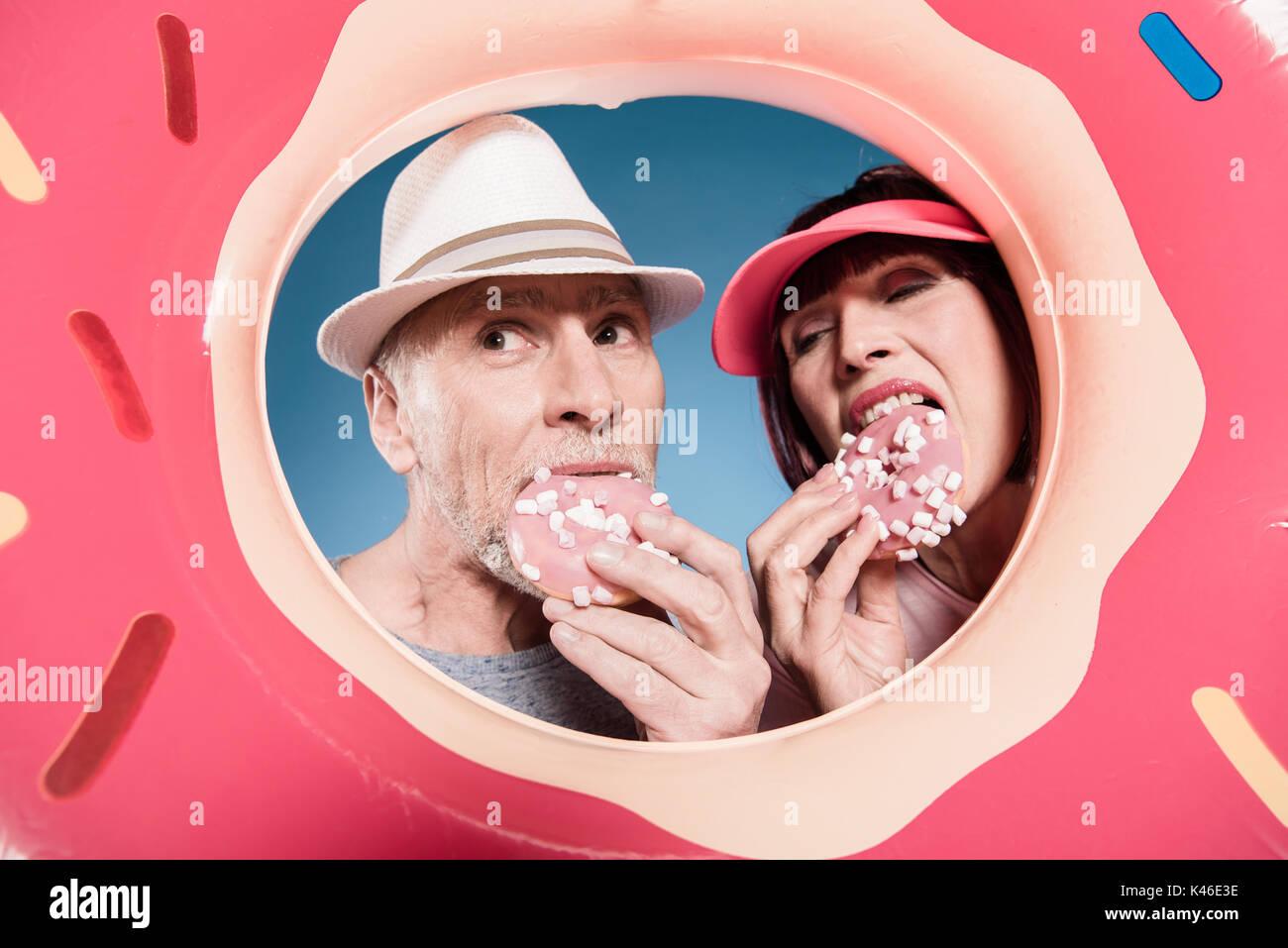 Portrait of elderly couple manger des beignets sucrés en tube de natation Photo Stock
