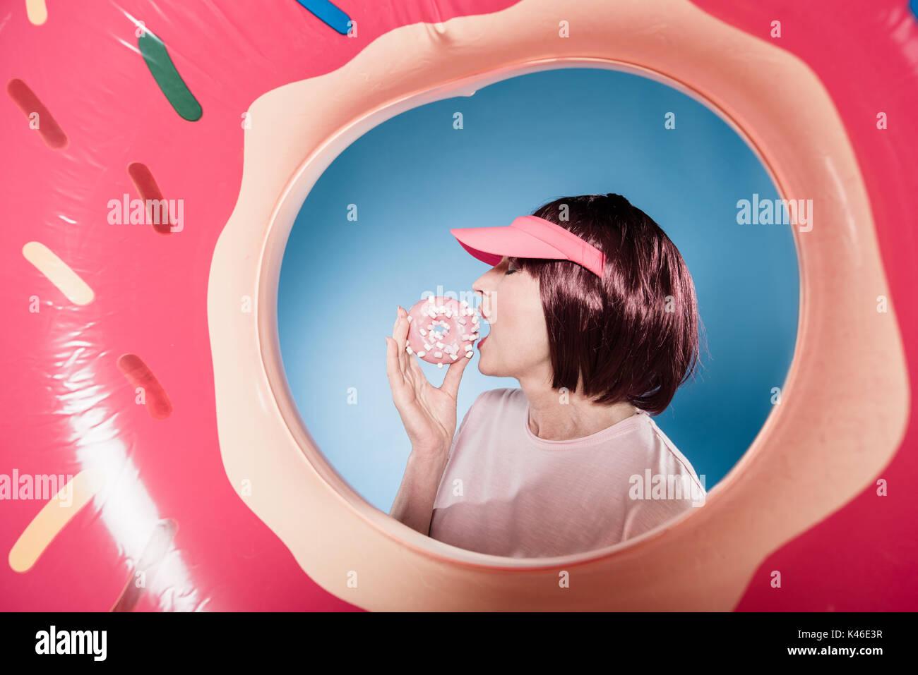 Femme élégante en beignet sucré alimentation tube natation Photo Stock
