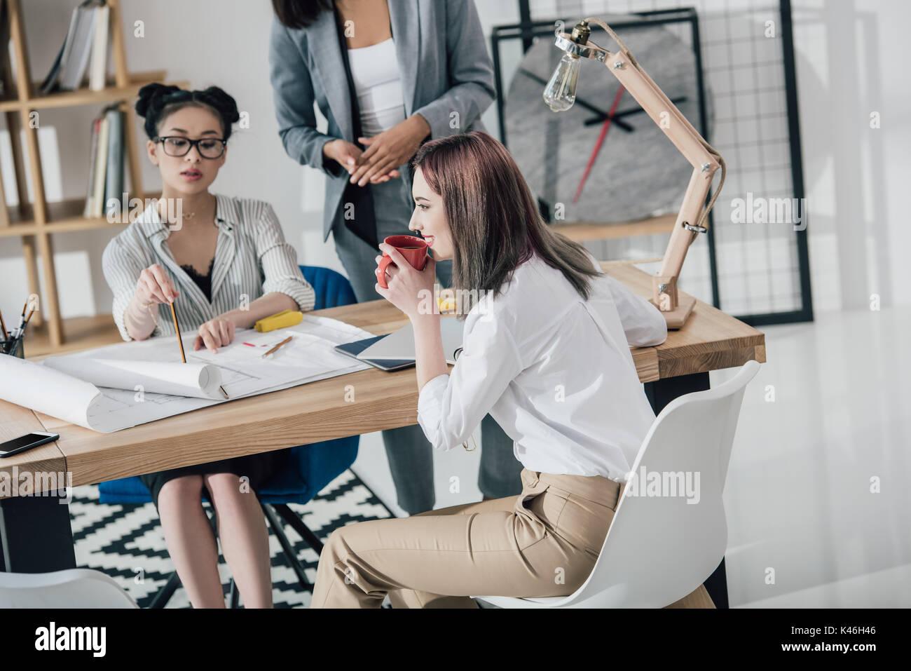 Groupe multiethnique de jeunes architectes professionnels travaillant avec blueprints in modern office Banque D'Images