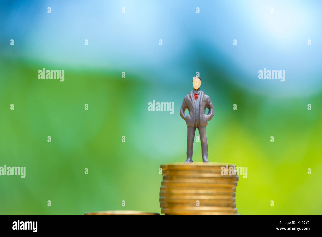 Les gens miniature, petits chiffres d'affaires se tenir sur des pièces. L'argent et des finances, la croissance de l'entreprise concept. L'accent peu profonds dans des tons doux. Photo Stock