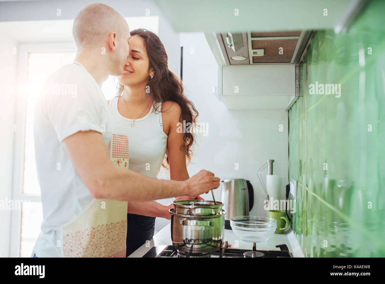 Happy young couple en train de préparer sur la cuisinière Photo Stock