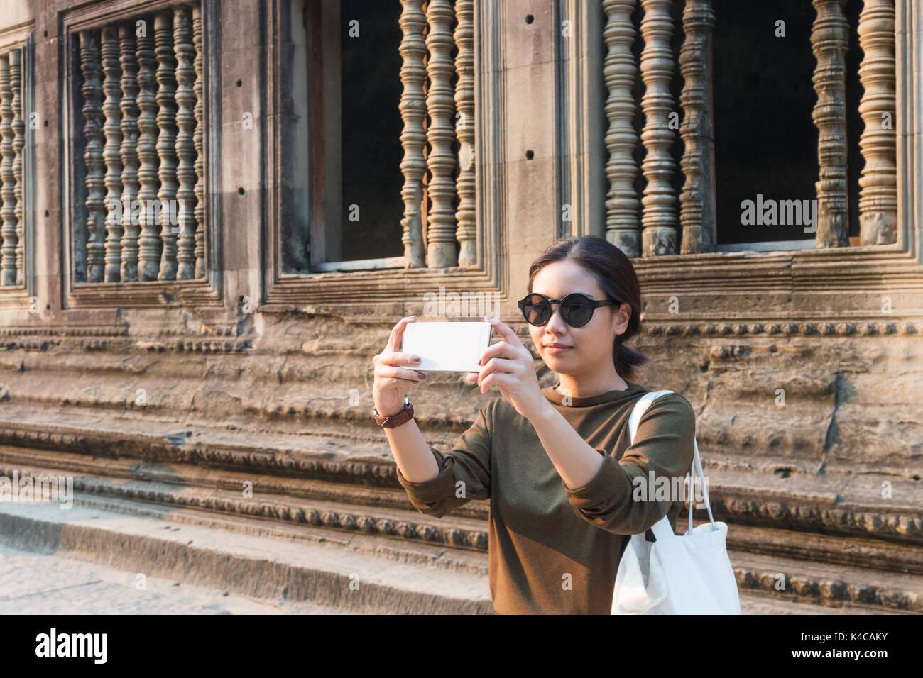Female traveler prenant des photos avec son smartphone à Angkor Wat siem reap Cambodge Photo Stock
