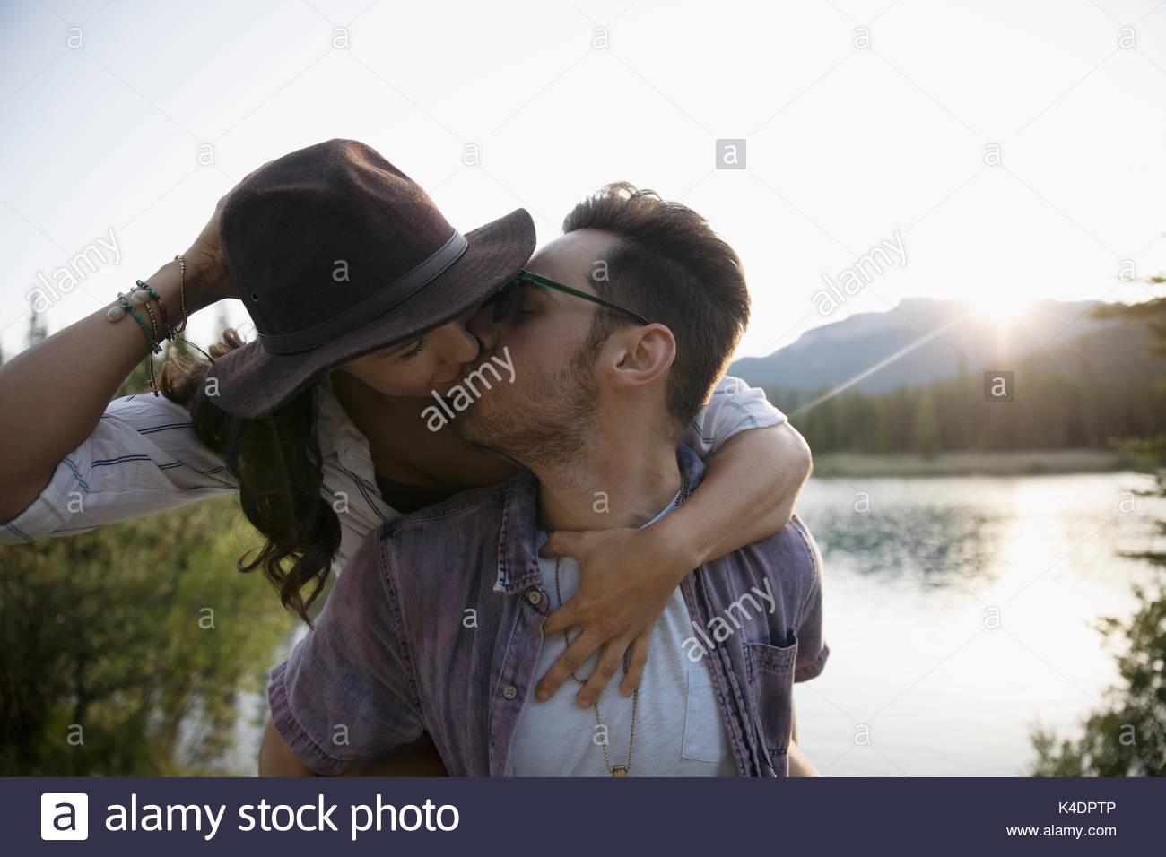 Couple romantique affectueuse sur le dos et les baisers d'été à Lakeside Photo Stock