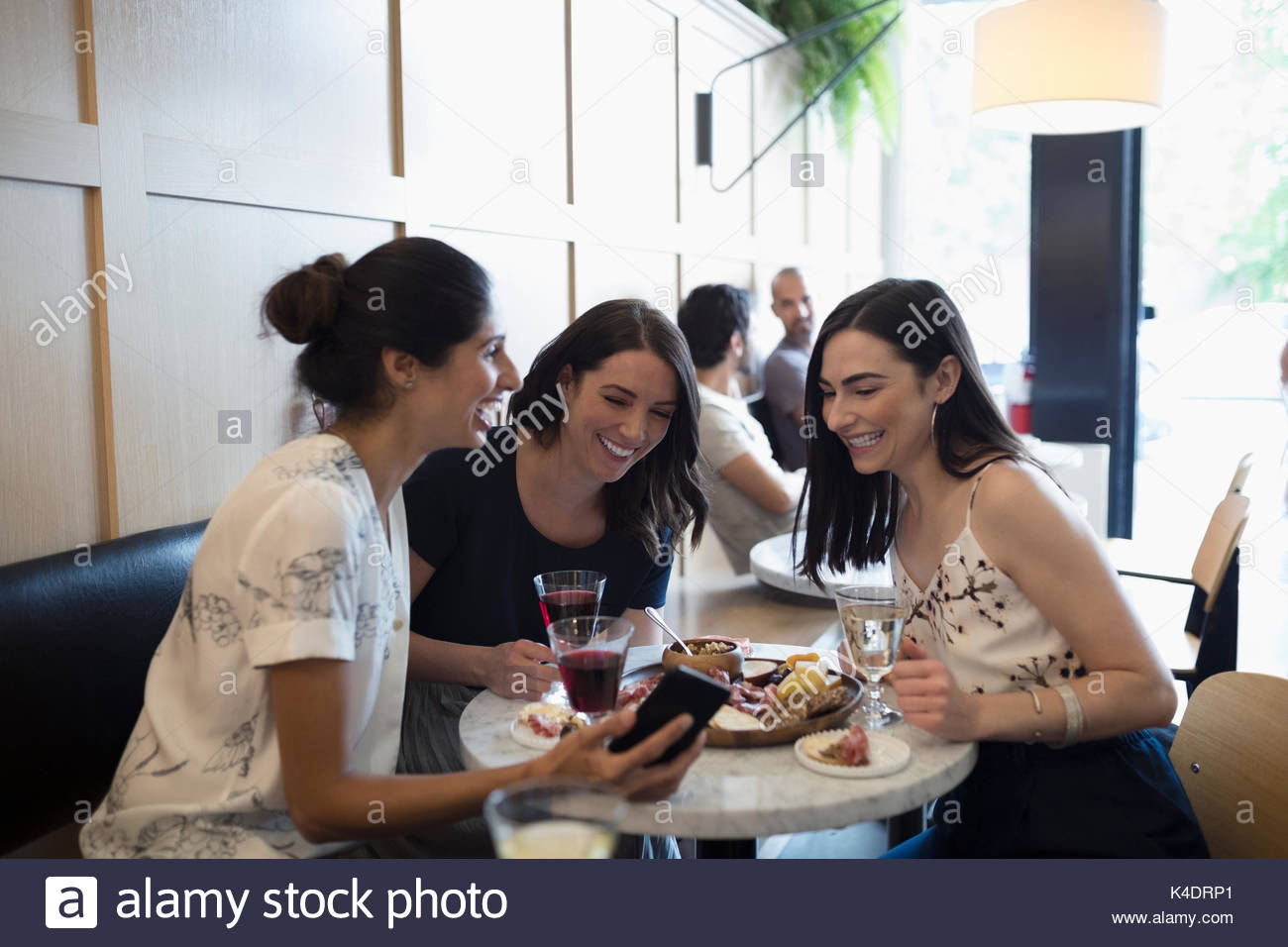 Smiling women friends drinking wine and using cell phone at cafe table Photo Stock