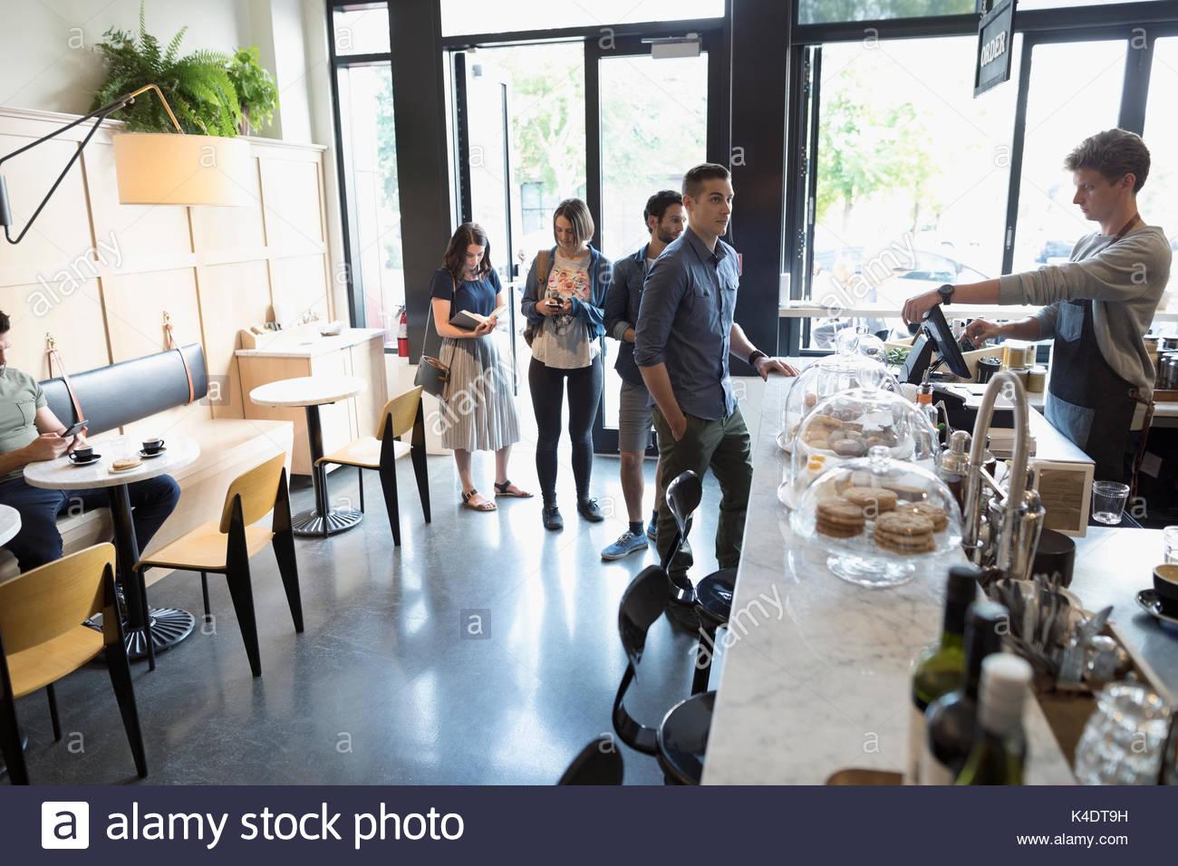 Travailleur homme aide les clients dans la file d'attente au comptoir de café Banque D'Images
